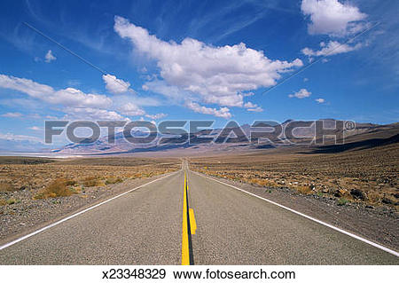Stock Photograph of Desert highway with drifting clouds x23348329.