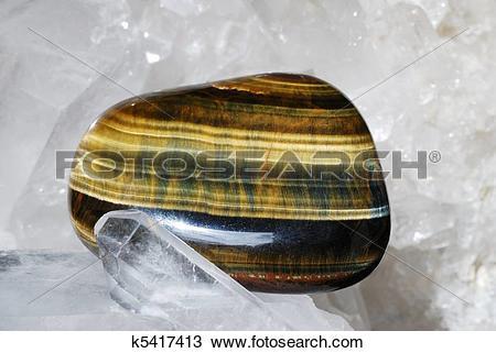 Stock Photo of Tiger eye laid on druze of quartz k5417413.