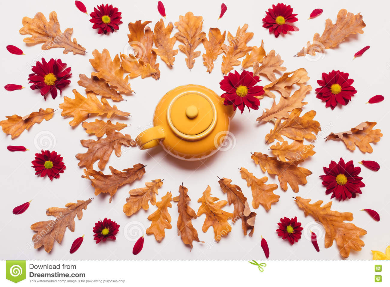 Composition Of Yellow Kettle, Dry Leaves And Red Flowers With Pe.