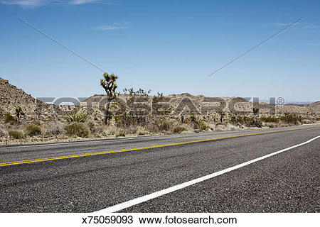 Stock Photo of a long empty street leads trhough a dry country.