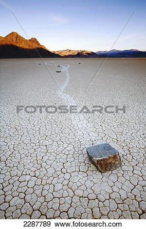 Stock Photograph of Rocks move across dry lake bed leaving trails.