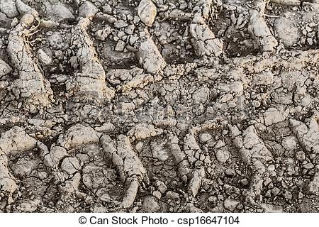 Stock Photography of Dry Cracked Mud With Tire Tracks.