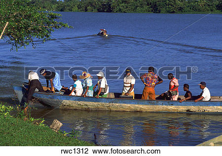 Stock Photo of Groupo f Garifuna people in dugout boat arriving at.