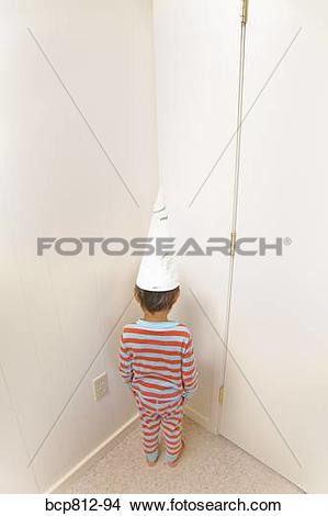 Stock Photo of Boy wearing dunce cap in corner bcp812.