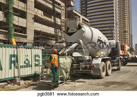 Stock Photography of Ready mixed concrete truck fills crane skip.