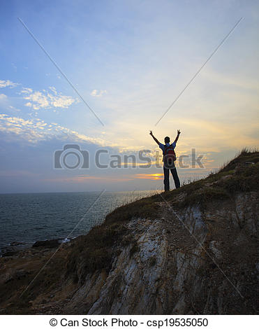 Stock Images of young man standing on rock clift and rising.