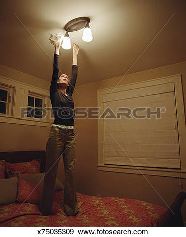 Stock Photograph of Young woman standing on bed to dust light.