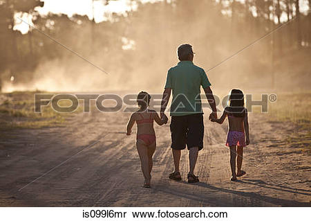 Stock Image of Father and daughters walking hand in hand on dust.