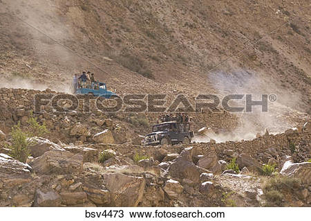 Stock Photo of Balti porters riding in jeeps on the dusty road to.