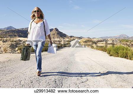 Stock Photo of Woman walking alone on dusty road u29913482.