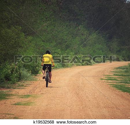 Pictures of young man riding mountain bike in dusty road use for.