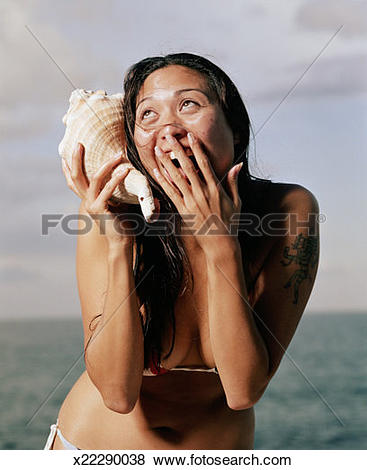 Pictures of Young woman in bikini holding conch shell to ear.