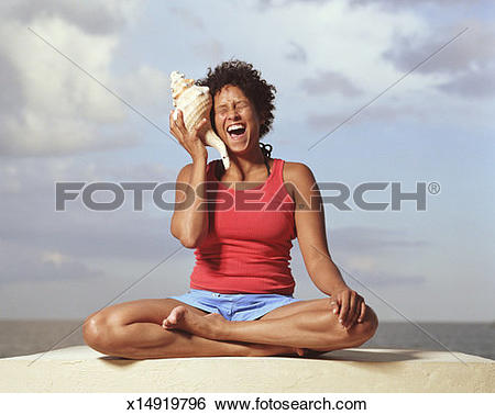 Stock Images of Woman holding conch shell to ear, laughing.