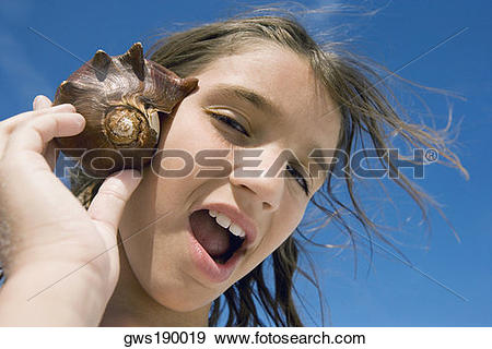 Stock Photograph of Portrait of a girl holding a conch shell to.