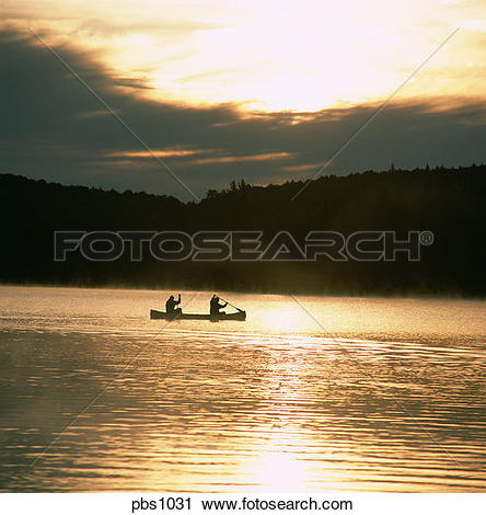 Stock Photography of Two canoeists paddling on a misty lake in the.