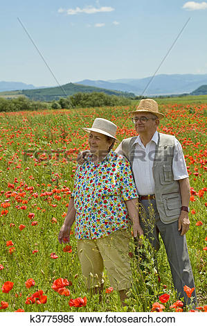 Stock Image of Senior couple on poppy field in early summer.