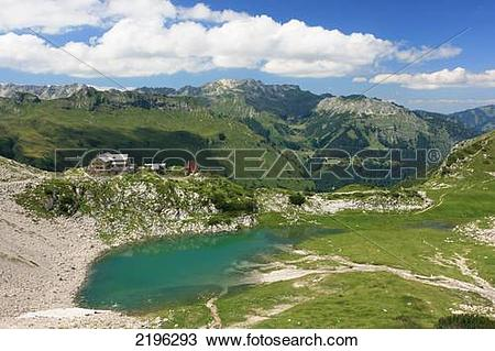 Stock Photo of House at lakeside with mountain range in background.