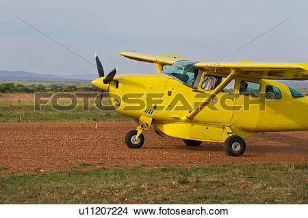 Stock Photo of Side view of yellow Cessna plane on dirt runway.