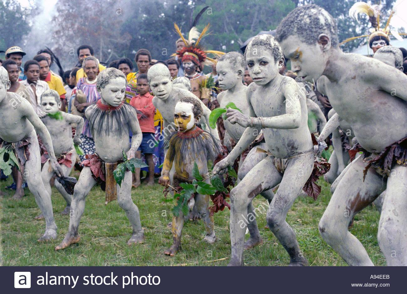 Children dancing as Asaro mudmen Asaroka Eastern Highlands Province.