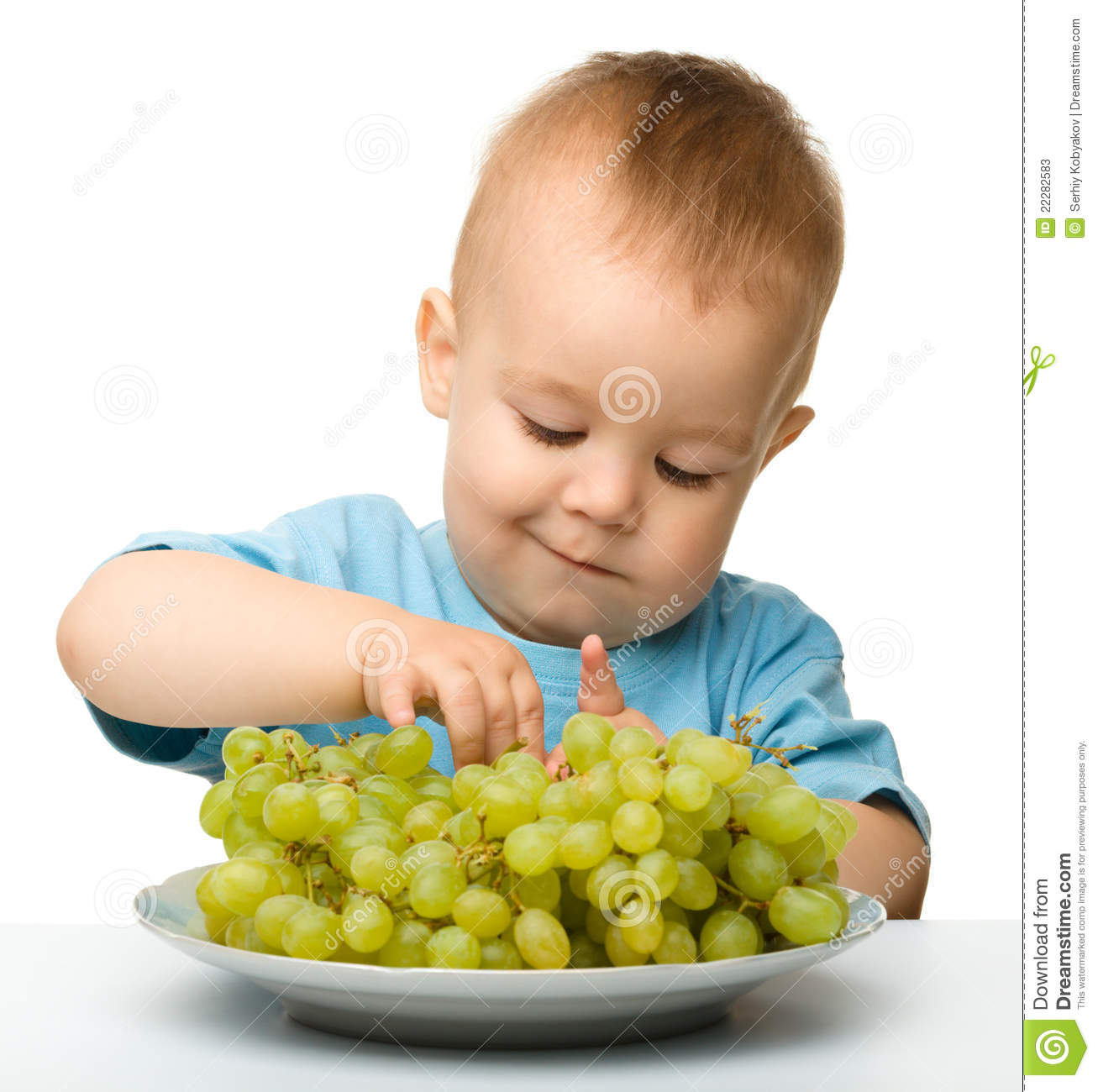 Little Boy Is Eating Grapes Stock Photos.