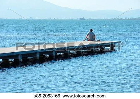 Stock Images of Man sitting on pier Ebro Delta, Tarragona.