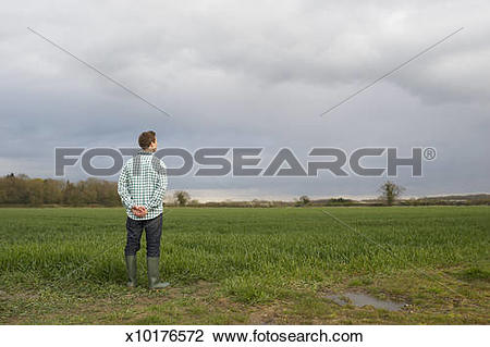 Stock Photo of Farmer at edge of field looking across land.