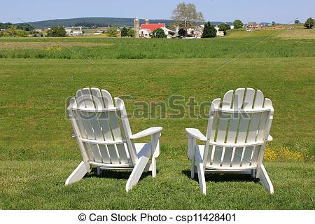 Stock Photography of Adirondack chairs on edge of field.