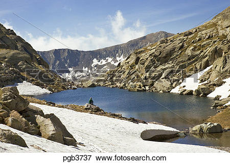 Picture of Parc National du Mercantour. Walker sits on a rock at.