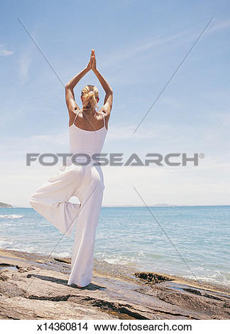 Stock Photo of Woman Doing Yoga By the Edge of the Sea x14360814.
