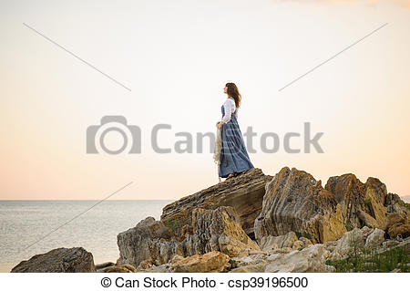 Stock Photography of girl on the edge of a cliff looking out to.