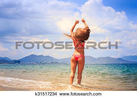 Stock Photo of blonde slim gymnast in bikini stands backside on.