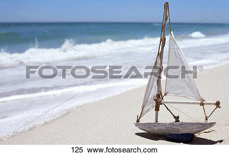 Stock Image of White toy sailing boat on sandy beach near water's.