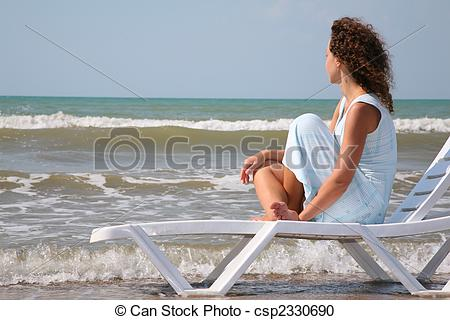 Stock Photography of young woman sits in the chaise lounge on the.