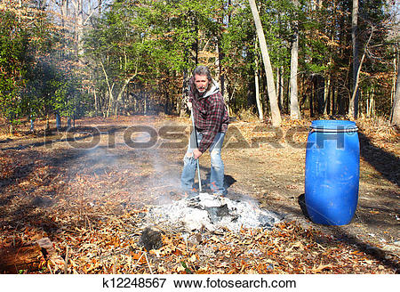 Picture of A man working a burning pile of trash and debris along.