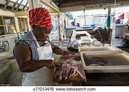 Pictures of Woman filleting flying fish in Bridgetown fish market.