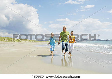 Stock Photography of Couple running with their son on beach.