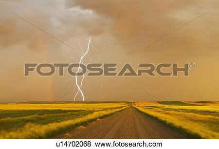 Pictures of electrical storm over gravel road between farmland.