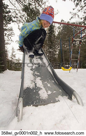 Stock Photo of Young girl playing in snow and sliding down.