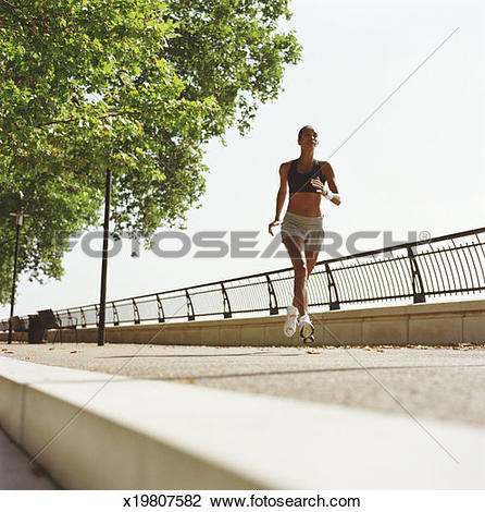Stock Photo of Woman running on embankment, low angle view.