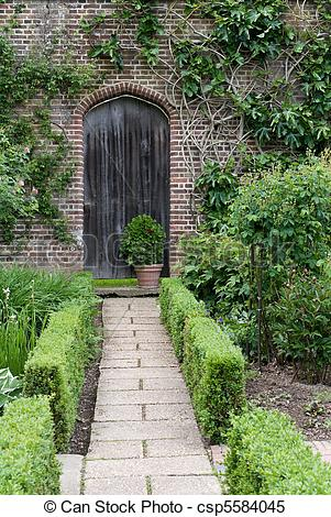 Stock Images of Secret garden. English garden path and door.