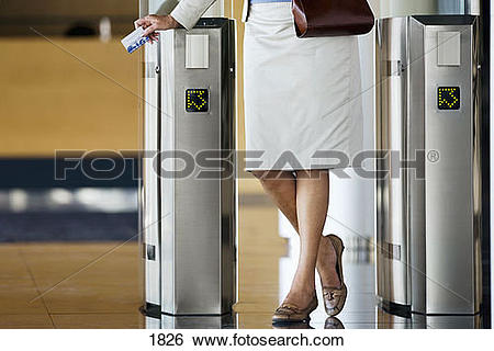Stock Images of Businesswoman swiping card in entrance barrier.