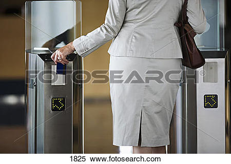 Stock Image of Businesswoman swiping card in entrance barrier.