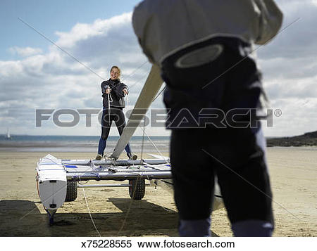 Stock Image of Couple erecting mast of catamaran on beach.
