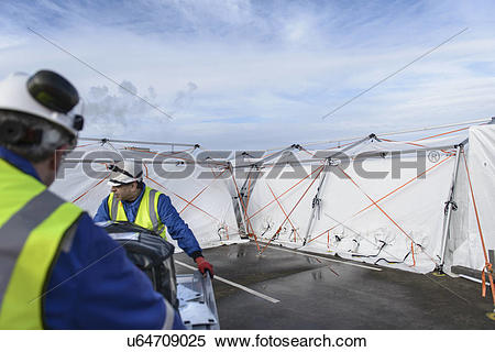 Stock Image of Emergency Response Team workers erecting tent.