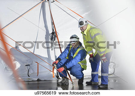 Stock Photograph of Emergency Response Team workers erecting tent.