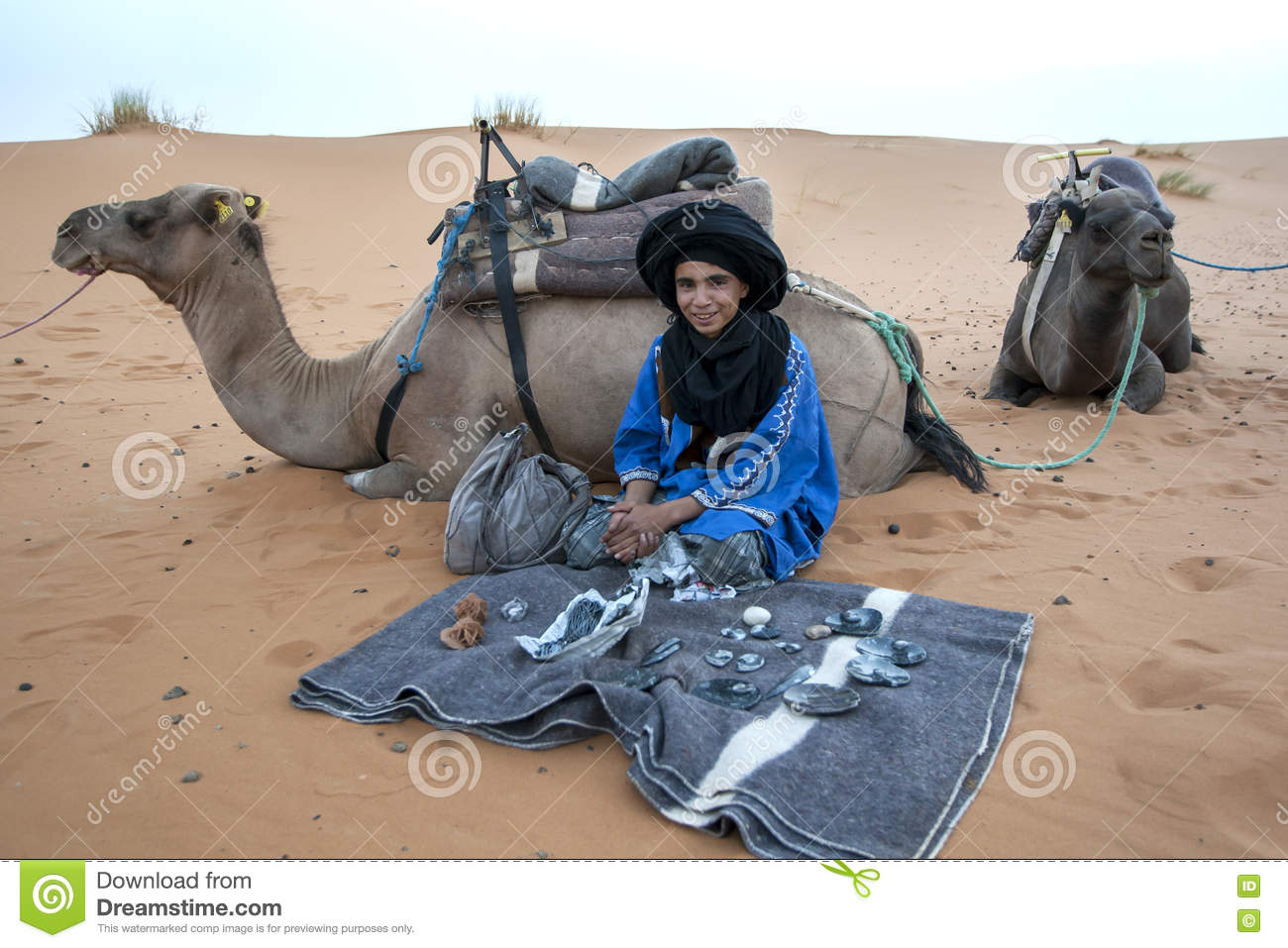 A Moroccan Boy Selling Souvenirs At Merzouga, Which Lies On The.