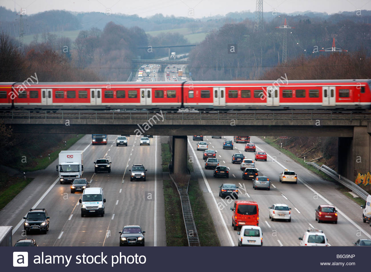 Local Train Is Crossing The Motorway A3 Rushhour Traffic On The.