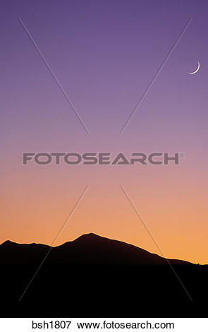 Picture of Crescent moon and evening light at dusk over silhouette.