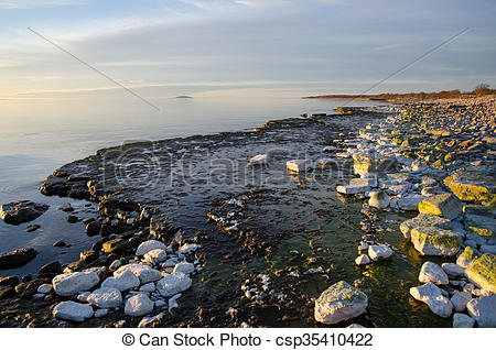 Stock Photo of Evening light colors by a flat rock coast.
