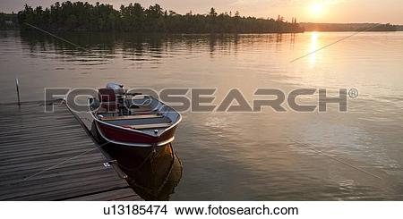 Stock Photo of Motorboat at the edge of a dock with the horizon.